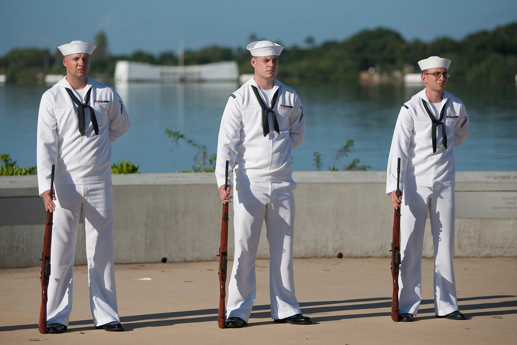 . With the USS Arizona in the background, Navy rifleman stand during the ceremony commemorating the 72nd anniversary of the attack on Pearl Harbor, Saturday, Dec. 7, 2013, in Honolulu.  (AP Photo/Marco Garcia)