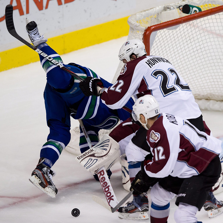 . Colorado Avalanche\'s Matt Hunwick, right, trips Vancouver Canucks\' Steve Pinizzotto, left, as Chuck Kobasew, bottom, gathers the puck during the third period of an NHL hockey game in Vancouver, British Columbia, on Thursday, March 28, 2013. (AP Photo/The Canadian Press, Darryl Dyck)
