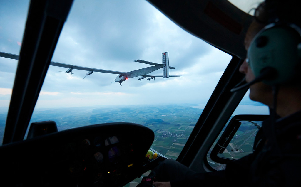. Solar Impulse  Andre Borschberg checks from his helicopter German test pilot Markus Scherdel steering the solar-powered Solar Impulse 2 aircraft during its maiden flight at its base in Payerne, Switzerland, Monday  June 2, 2014. (AP Photo/Denis Balibouse,pool)