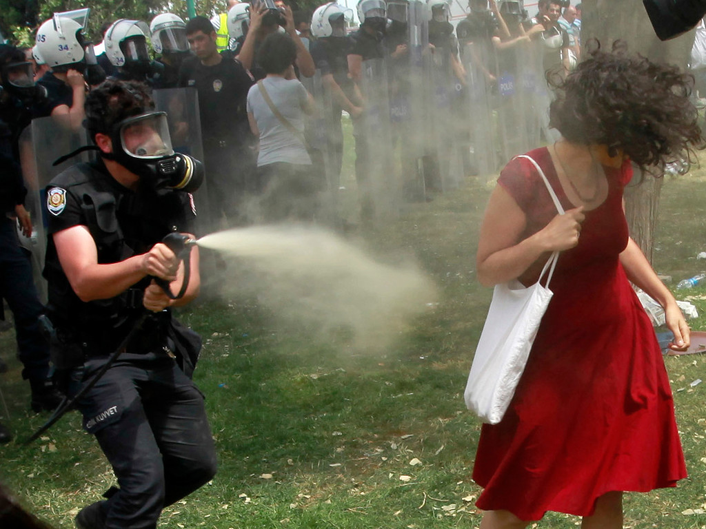 . A Turkish riot policeman uses tear gas against a woman as people protest against the destruction of trees in a park brought about by a pedestrian project, in Taksim Square in central Istanbul May 28, 2013.In her red cotton summer dress, necklace and white bag slung over her shoulder she might have been floating across the lawn at a garden party; but before her crouches a masked policeman firing teargas spray that sends her long hair billowing upwards. Endlessly shared on social media and replicated as a cartoon on posters and stickers, the image of the woman in red has become the leitmotif for female protesters during days of violent anti-government demonstrations in Istanbul.  Picture taken May 28.  REUTERS/Osman Orsal