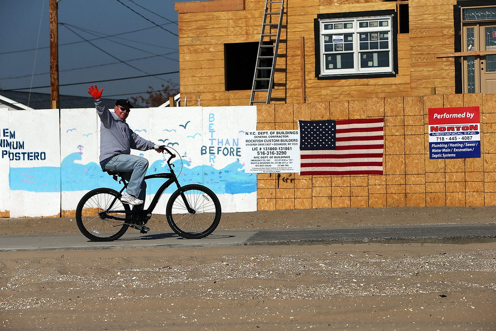 . A man rides his bike by newly-contructed homes in the Breezy Point neighborhood on the one-year anniversary of Hurricane Sandy on October 29, 2013 in the Queens borough of New York City.   (Photo by Spencer Platt/Getty Images)