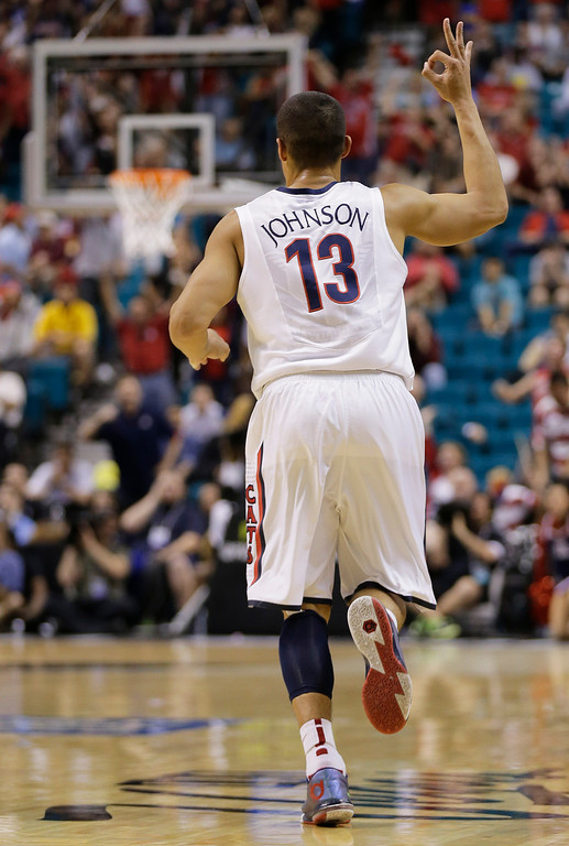 . Arizona\'s Nick Johnson holds up three fingers after hitting a 3-point basket during the first half of an NCAA college basketball game in the semifinals of the Pac-12 Conference on Friday, March 14, 2014, in Las Vegas. (AP Photo/Julie Jacobson)
