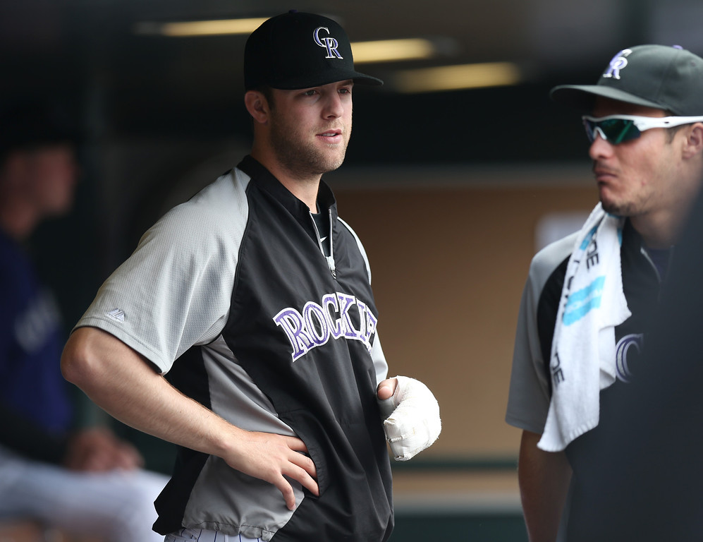 . Colorado Rockies starting pitcher Jordan Lyles, left, who was injured earlier this week, chats with injured third baseman Nolan Arenado in the dugout as the Rockies face the Los Angeles Dodgers in the fifth inning of a baseball game in Denver on Saturday, June 7, 2014. (AP Photo/David Zalubowski)