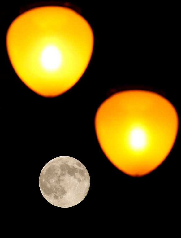 ". The full moon rises behind street lamps in Tbilisi, Georgia on June 23, 2013. The largest full moon of the year called a ""super moon\"" will light up the night sky this weekend. REUTERS/David Mdzinarishvili"