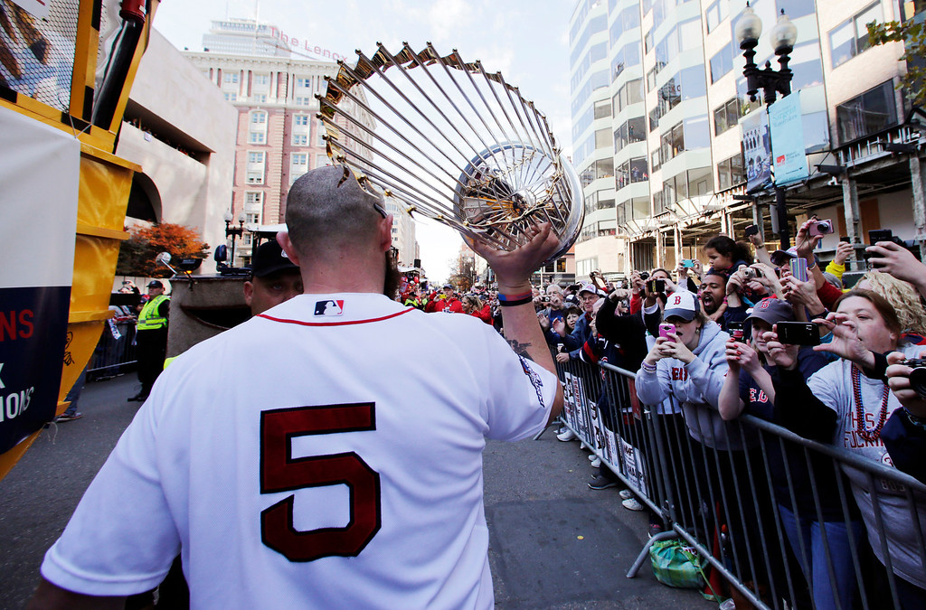 . Boston Red Sox\'s Jonny Gomes carries the 2013 World Series trophy and a team jersey to the finish line of the Boston Marathon, in honor of those affected by the bombings, as they stopped the parade in celebration of the baseball team\'s World Series win, Saturday, Nov. 2, 2013, in Boston. (AP Photo/Charles Krupa)