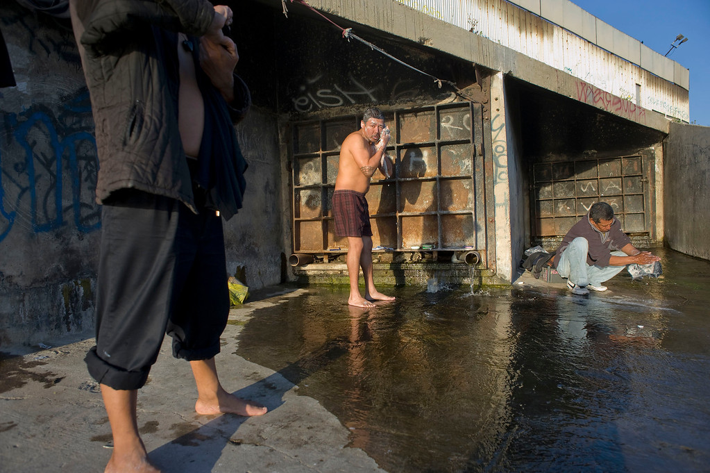 . People wash and bathe in clean water that flows from a drain originating in the US in the Tijuana River canal, which has become home to hundreds of people deported from the US, in Tijuana, Mexico, 27 March 2013. Heightened US border security and record numbers of deportations from the US have created a growing population of people who live homeless in Mexican cities that border with the United States. Many had lived for years undocumented in the US and have little or no family and other support in Mexico, and are subject to fall into depression, substance abuse and crime. Tijuana, Mexico, borders on the US city of San Diego, California.  EPA/DAVID MAUNG