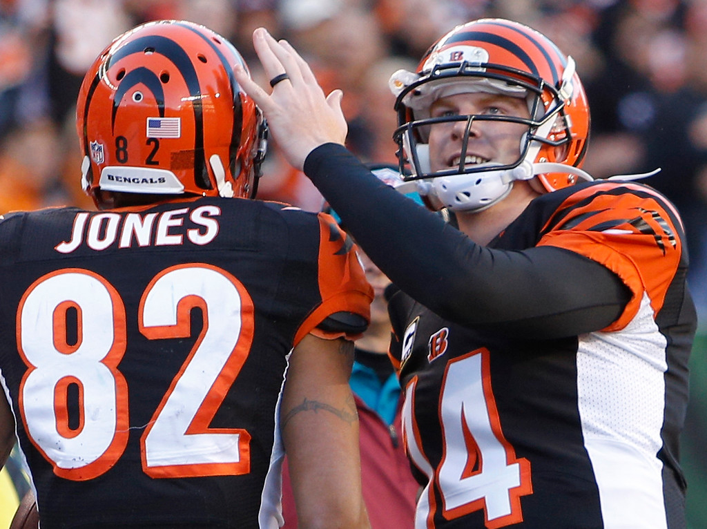 . Cincinnati Bengals quarterback Andy Dalton (14) congratulates wide receiver Marvin Jones (82) after they combined on their third touchdown pass of the game in the first half of an NFL football game against the New York Jets, Sunday, Oct. 27, 2013, in Cincinnati. (AP Photo/David Kohl)