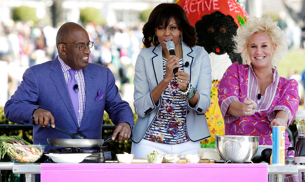 . U.S. first lady Michelle Obama (C) sings and dances as she cooks with television personalities Al Roker (L) and Anne Burrell (R) at the healthy eating station during the Easter Egg Roll on the South Lawn of the White House in Washington, April 1, 2013. REUTERS/Jonathan Ernst