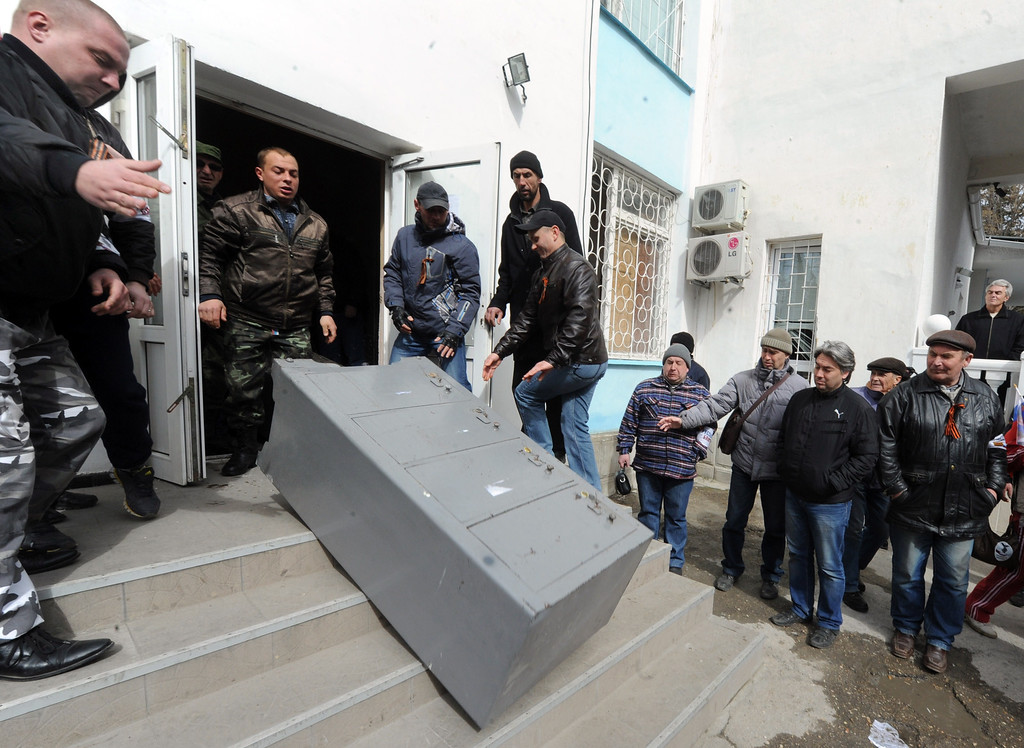 . Pro-Moscow militants throw a safe out of the Ukrainian navy headquarters in Sevastopol on March 19, 2014.  AFP PHOTO/  VIKTOR DRACHEV/AFP/Getty Images