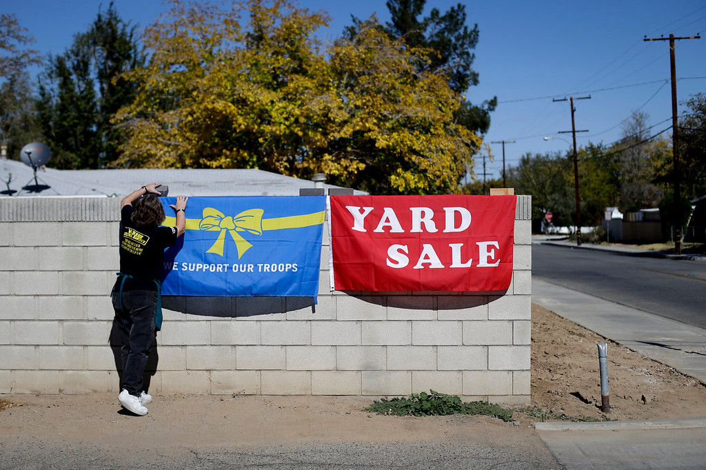 . Volunteer Rose Sliepka removes a flag after a yard sale held to benefit Jerral Hancock, a 27-year-old Iraq war veteran who lost his left arm and was paralyzed from the waist down in a bomb explosion in Iraq, on Saturday, Oct. 26, 2013, in Lancaster, Calif. When the seniors in Jamie Goodreau\'s high school history class learned Hancock was once stuck in his modest mobile home for months when his handicapped-accessible van broke down, they decided to build him a new house from the ground up.  It would be their end-of-the-year project to honor veterans, something Goodreau\'s classes have chosen to do every year for the past 15 years. (AP Photo/Jae C. Hong)