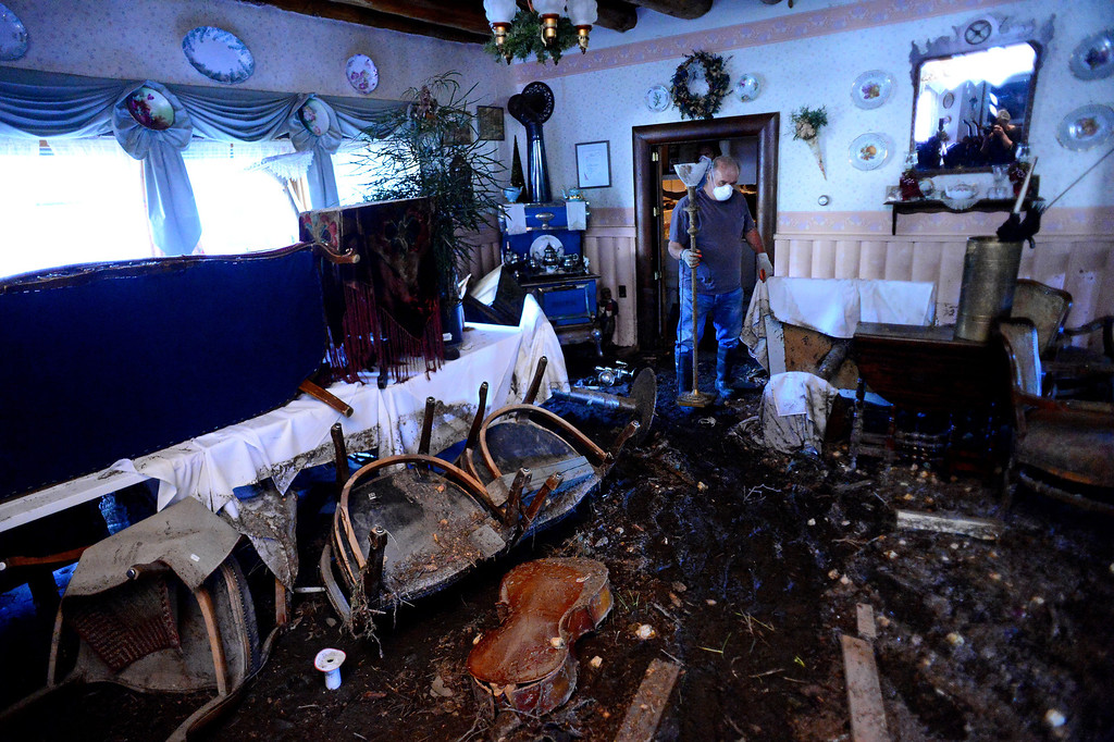 . GLEN HAVEN, CO - OCTOBER 8: Glen Haven Inn owner Tom Sellers looks at what remains on the inside of their historic Glen Haven Inn in Glen Haven, CO on October 8, 2013.  The Inn was one of the only businesses that actually made it in the town but has been inundated with mud and debris.  The water line along the walls suggest that the flood waters reached at least four feet inside the building. (Photo By Helen H. Richardson/ The Denver Post)