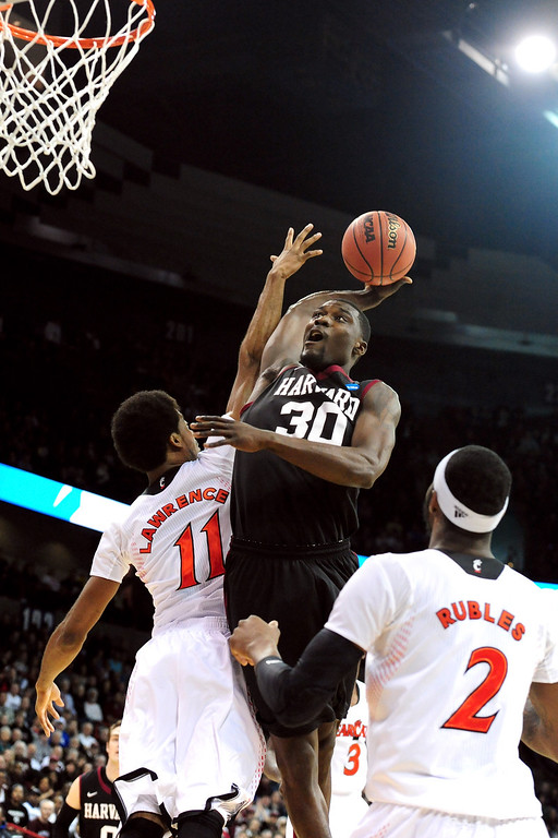 . Kyle Casey #30 of the Harvard Crimson dunks the ball over Jermaine Lawrence #11 and Titus Rubles #2 of the Cincinnati Bearcats during the second round of the 2014 NCAA Men\'s Basketball Tournament at Spokane Veterans Memorial Arena on March 20, 2014 in Spokane, Washington.  (Photo by Steve Dykes/Getty Images)