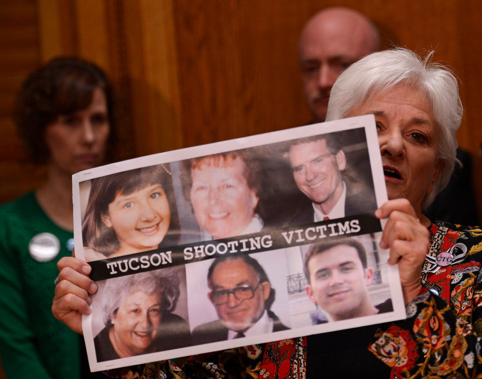 . Patricia Maisch, who helped prevent the Tucson shooter from reloading, holds photos of the six victims as she speaks to media before testifying on a universal background check bill for private gun sales, March, 04, 2013, at the Colorado State Capitol. (Photo By RJ Sangosti/The Denver Post)