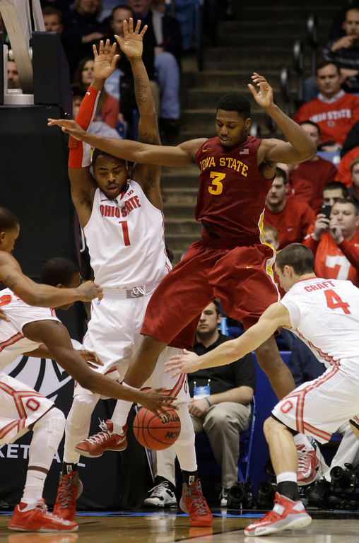 . Iowa State forward Melvin Ejim rebounds against Ohio State guard Aaron Craft (4) and Ohio State forward Deshaun Thomas (1) in the second half of a third-round game of the NCAA college basketball tournament, Sunday, March 24, 2013, in Dayton, Ohio. (AP Photo/Al Behrman)