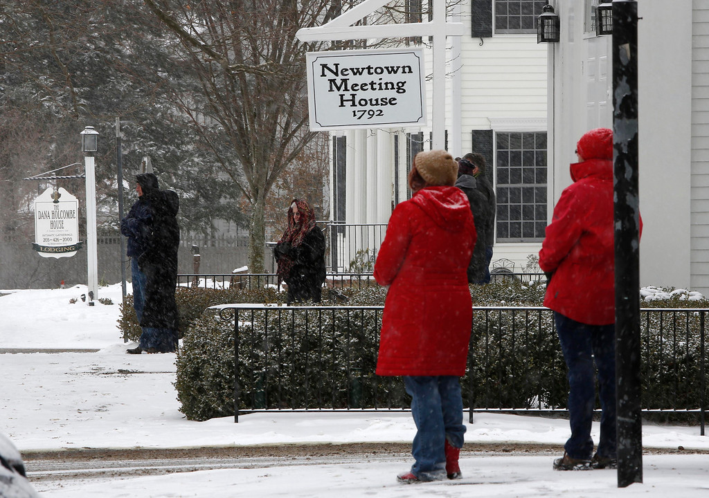 . People pause in silence while church bells ring in honor of the victims of the Sandy Hook massacre, Saturday, Dec. 14, 2013, in Newtown, Conn.  Newtown is asking that people honor the victims one the one-year anniversary in ways that are quiet and personal. (AP Photo/Robert F. Bukaty)