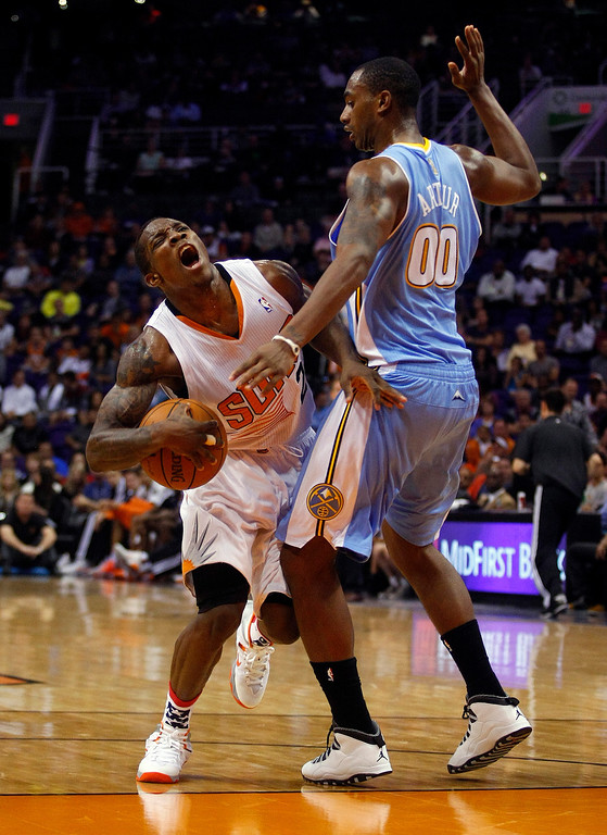 . Phoenix Suns point guard Eric Bledsoe (2), left, reacts after getting fouled by Denver Nuggets power forward Darrell Arthur (00) in the third quarter during an NBA basketball game on Friday, Nov. 8, 2013, in Phoenix. The Suns defeated the Nuggets 114-93. (AP Photo/Rick Scuteri)
