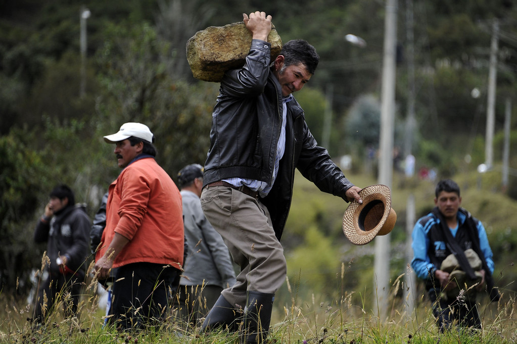 . A Colombian farmer demanding government subsidies and greater access to land helps block the road in La Calera, Cundinamarca department, on August 23, 2013. A five-day-old farmworkers\' protest in Colombia claimed its first fatality Friday when a man on a motorcycle crashed and died at a roadblock, police said Friday. Since the protests began Monday, farmworkers have closed roads at dozens of points in across the country, blocking the passage of cargo trucks and other vehicles from makeshift camps erected on sides of roads.  EITAN ABRAMOVICH/AFP/Getty Images