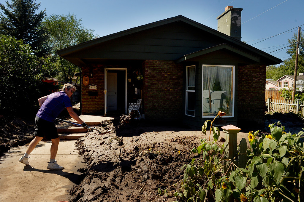 . Dan Reagin shovels mud outside the home of Sharen Kelling  in Lyons,  CO September 20, 2013. Friday was the second day residents were allowed to return to their homes.  (Photo By Craig F. Walker / The Denver Post)