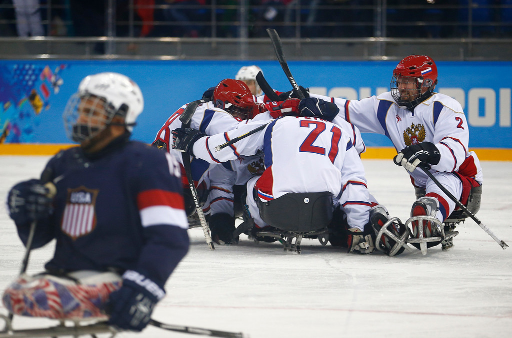 . Russia players celebrate a goal during an ice sledge hockey match between United States and Russia at the 2014 Winter Paralympics in Sochi, Russia, Tuesday March 11, 2014. (AP Photo/Pavel Golovkin)
