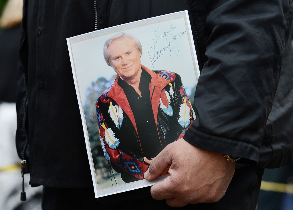 . Billy Smith of Hendersonville, Tenn., holds a photograph signed by George Jones in 1990 while waiting to enter the Grand Ole Opry House for Jones\' funeral on Thursday, May 2, 2013, in Nashville, Tenn. Jones, a country music legend who had No. 1 hits in four separate decades, died April 26. (AP Photo/Mark Zaleski)
