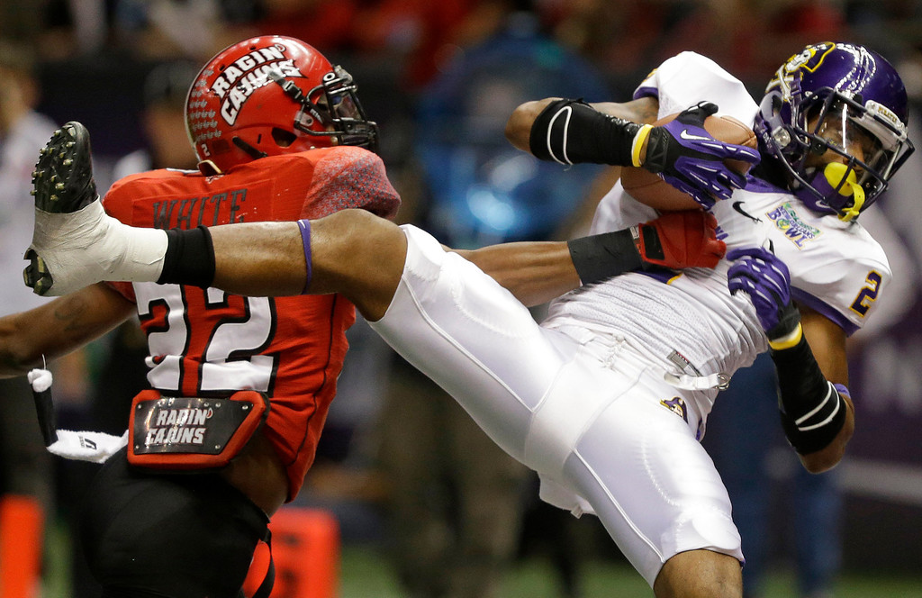 . East Carolina wide receiver Justin Hardy (2) catches a touchdown pass as Louisiana-Lafayette cornerback Melvin White (22) defends in the first half of the New Orleans Bowl, an NCAA college football game in New Orleans, Saturday, Dec. 22, 2012. (AP Photo/Bill Haber)