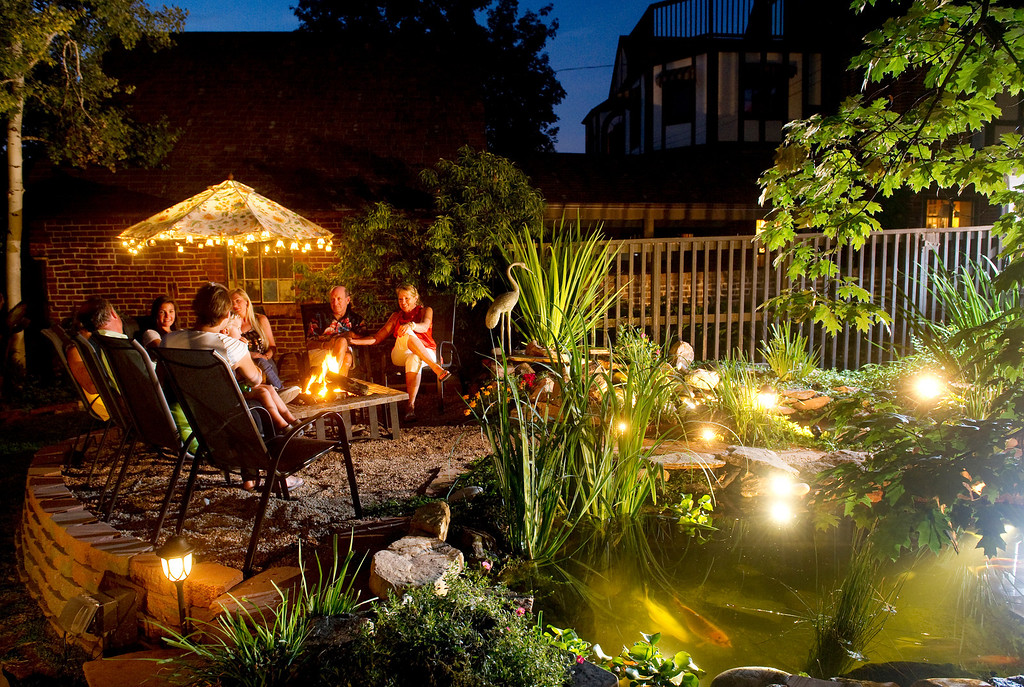 . Becky Peters-Combs, right, and husband Keith Combs, second from right, gather with friends of their youngest daughter one evening last summer. The ponds become even more spectacular on summer nights. (Cyrus McCrimmon, The Denver Post)