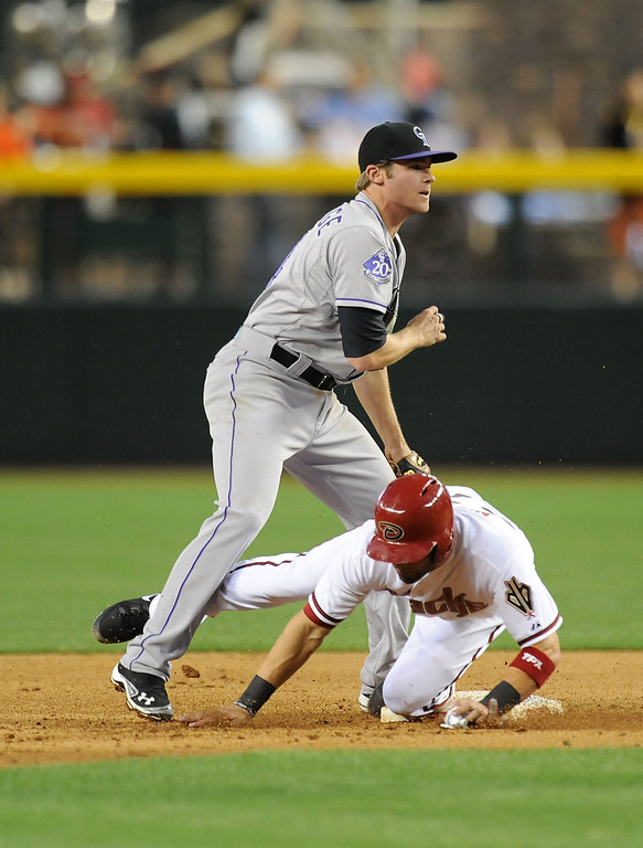 . PHOENIX, AZ - APRIL 25:  Josh Rutledge #14 of the Colorado Rockies turns a double play as Cliff Pennington #4 of the Arizona Diamondbacks slides into seconed base at Chase Field on April 25, 2013 in Phoenix, Arizona.  (Photo by Norm Hall/Getty Images)