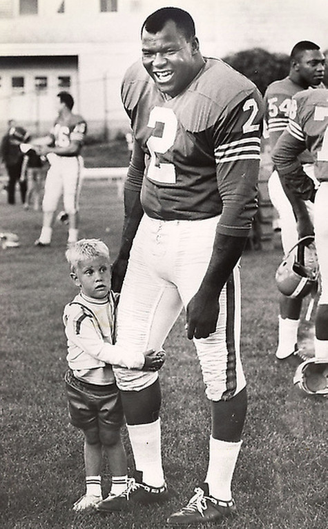 . In this August 1965 file photo, 3-year-old Jay Gomer wraps his arms around the leg of Denver Broncos fullback Cookie Gilchrist in Denver. Former American Football League star Gilchrist has died of cancer at 75. Nephew Thomas Gilchrist says his uncle died Monday, Jan. 10, 2011, at an assisted living facility near Pittsburgh. Gilchrist spent three seasons in Buffalo, two in Denver and one in Miami. (AP Photo/File)