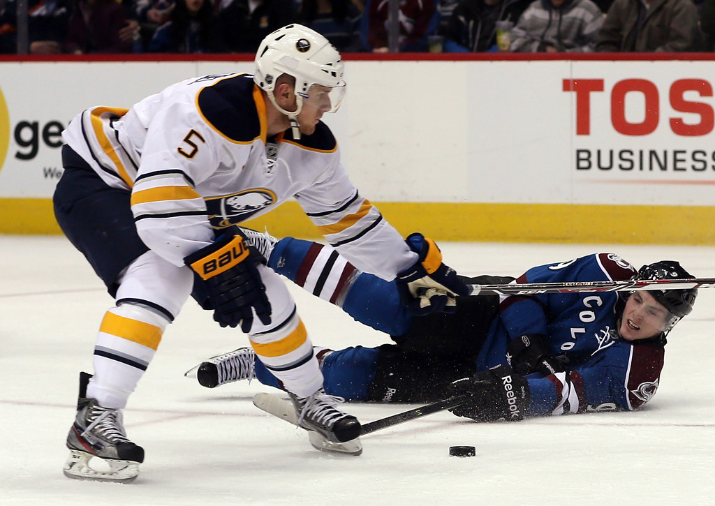 . Colorado Avalanche center Matt Duchene, right, struggles to control puck as he falls during a rush to the net while Buffalo Sabres defenseman Chad Ruhwedel covers in the second period of an NHL hockey game in Denver, Saturday, Feb. 1, 2014. (AP Photo/David Zalubowski)