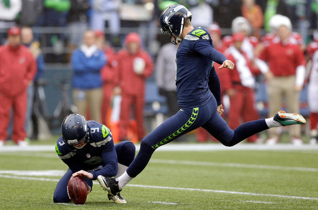 . Seattle Seahawks kicker Steven Hauschka, right, kicks a field goal as Seahawks punter Jon Ryan holds, in the first half of an NFL football game against the Arizona Cardinals, Sunday, Dec. 22, 2013, in Seattle. (AP Photo/Elaine Thompson)