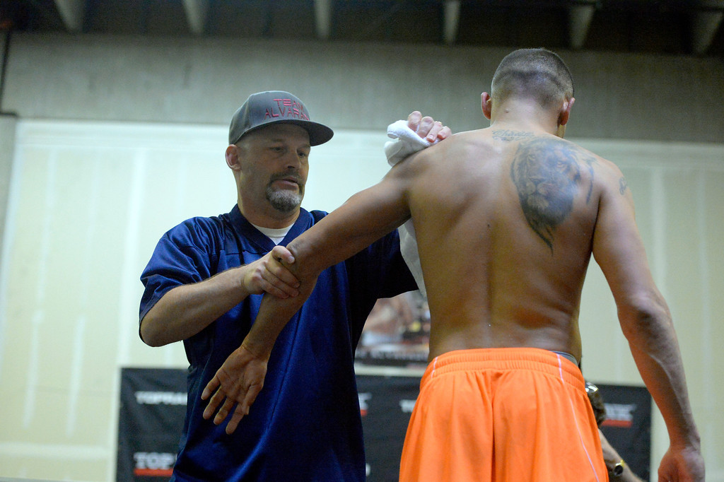 """. DENVER, CO - OCTOBER 15: Colorado\'s only reigning Champion \""""Mile High\"""" Mike Alvarado gets wiped down by Trainer Shann Vilhauer after his media workout day at Delgado\'s Gym October 15, 2013 as he gets ready for his fight with the Russian Provodnikov at 1st Bank Center. (Photo by John Leyba/The Denver Post)"""