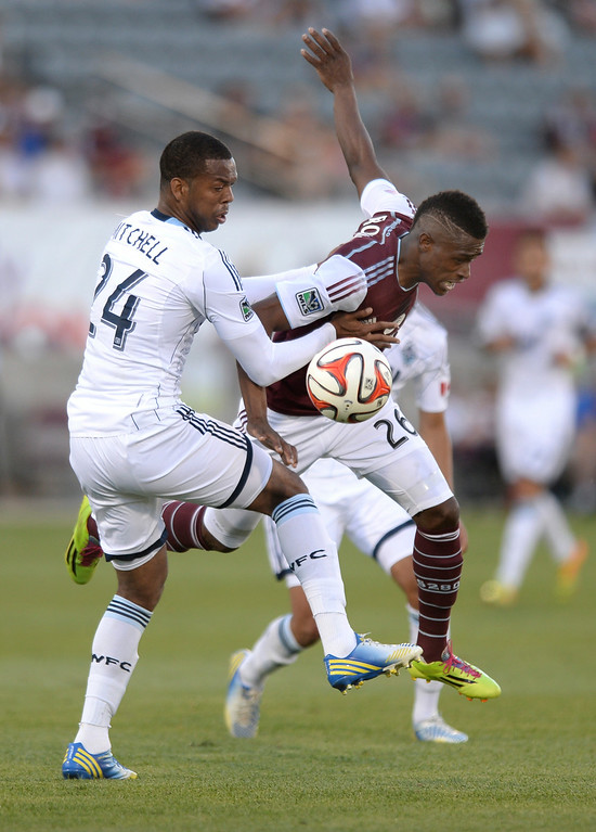 . COMMERCE CITY, CO - JUNE 28: Colorado forward Deshorn Brown (26) tried to get past Vancouver defender Carlyle Mitchell (24) in the first half. The Colorado Rapids defeated the Vancouver Whitecaps 2-0 at Dick\'s Sporting Goods Park Saturday night, June 28, 2014.  Photo by Karl Gehring/The Denver Post