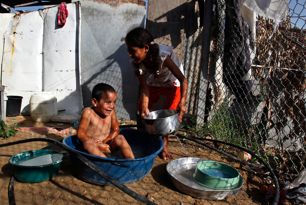 . In this Thursday, Sept. 12, 2013 photo, Manar Alwadiya, 12, right, gives Oday, 4, a bath in the yard of their family house in Gaza City. Most of the clothes and food for the extended family of 38 people comes from donations. The family is among the some 45 percent of Gazans who live in dire poverty, defined by the United Nations as living on less than $2 a day. (AP Photo/Adel Hana)
