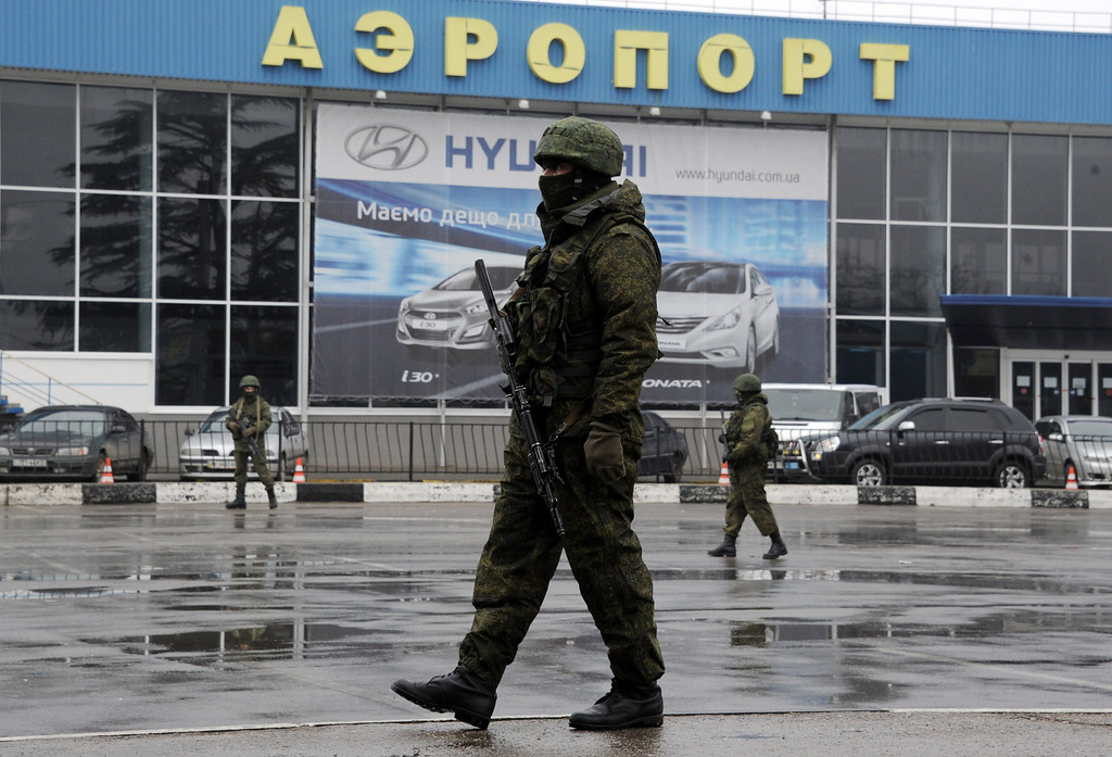 ". Unidentified armed men patrol outside of Simferopol airport, on February 28, 2014. Ukraine accused today Russia of staging an ""armed invasion\"" of Crimea and appealed to the West to guarantee its territorial integrity after pro-Moscow gunmen took control of the peninsula\'s main airport.AFP PHOTO / VIKTOR DRACHEV/AFP/Getty Images"