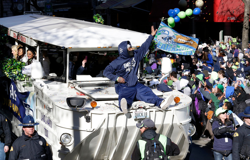 . Seattle Seahawks\' running back Marshawn Lynch throws pieces of candy while riding on the hood of a vehicle during the Super Bowl champions parade on Wednesday, Feb. 5, 2014, in Seattle. (AP Photo/Ted S. Warren)