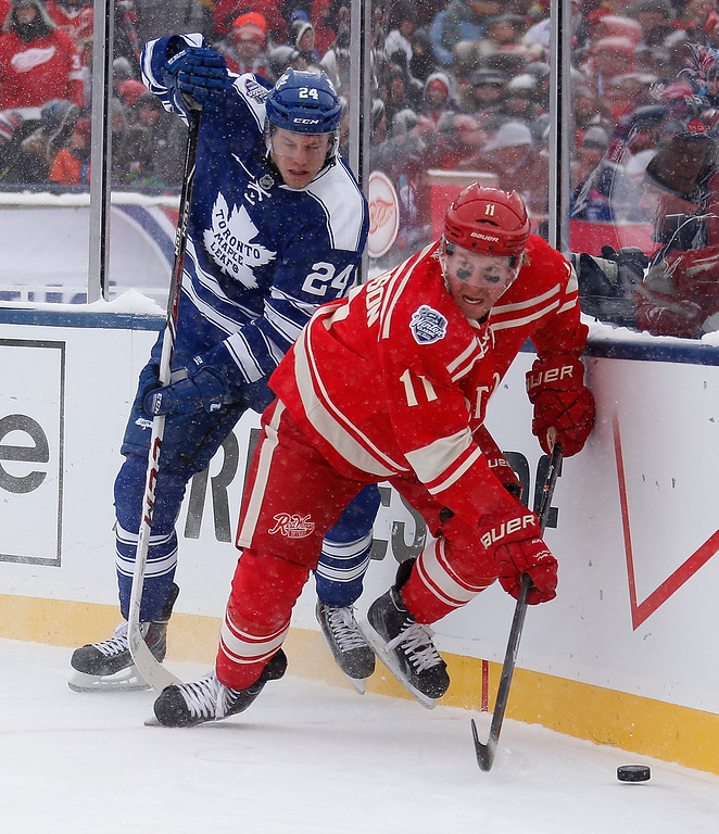 . Daniel Alfredsson #11 of the Detroit Red Wings controls the puck in front of Peter Holland #24 of the Toronto Maple Leafs in the second period during the 2014 Bridgestone NHL Winter Classic at Michigan Stadium on January 1, 2014 in Ann Arbor, Michigan. (Photo by Gregory Shamus/Getty Images)