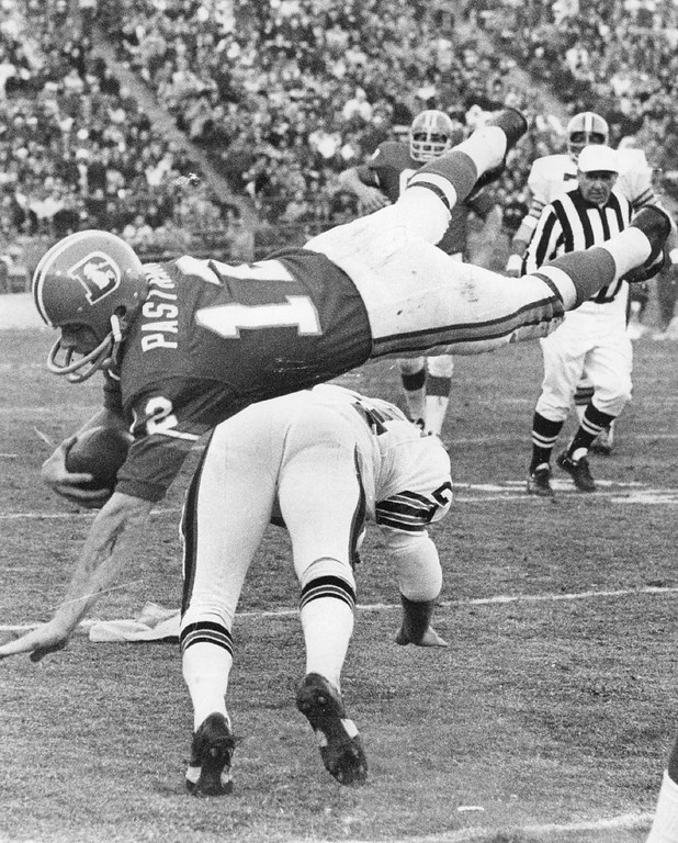 . Broncos Quarterback upended by Cleveland Safety in second half. Cleveland\'s Ernie Kellerman (24) undercuts Denver\'s Al Pastrana (12) in front of Broncos\' bench. 1970.  (Photo by Barry Staver/Denver Post)
