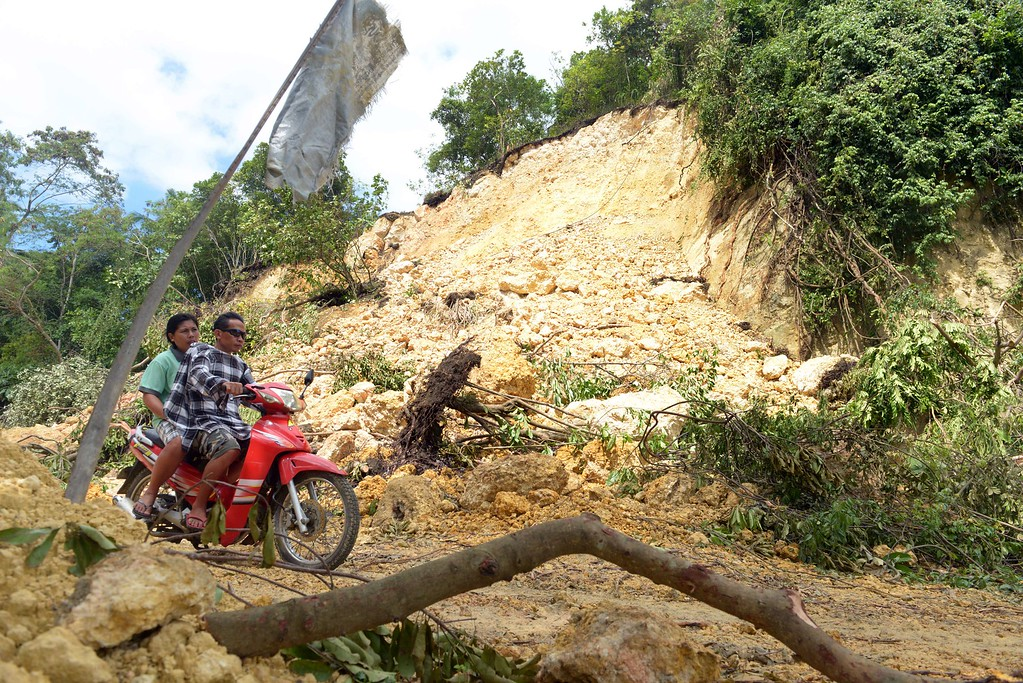 . A motorcycle pass by a landslide and a damaged road in the village of Cantam-is, Bohol on October 17, 2013, after a 7.1-magnitude earthquake that hit the central Philippine island of Bohol on October 15, 2013 killing 161 people.      AFP PHOTO / Jay DIRECTO/AFP/Getty Images