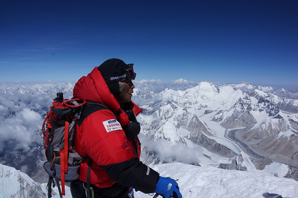 . Eighty-year-old Japanese extreme skier Yuichiro Miura, right, who has had four heart operations in recent years, stands atop the summit of Mount Everest as he becomes the oldest person to climb the world\'s tallest mountain Thursday, May 23, 2013. Miura, who also conquered the 29,035-foot (8,850-meter) peak when he was 70 and 75, reached the summit at 9:05 a.m. local time, according to a Nepalese mountaineering official and Miura\'s Tokyo-based support team. (AP Photo/MIURA DOLPHINS CO., LTD.)
