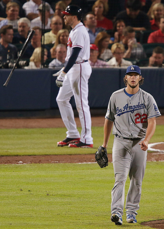 . Los Angeles Dodgers starting pitcher Clayton Kershaw (22) walks to the mound after striking out Atlanta Braves first baseman Freddie Freeman, rear,in the sixth inning of Game 1 of the National League division series, Thursday, Oct. 3, 2013, in Atlanta. (AP Photo/Dave Martin)
