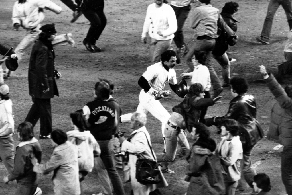 . New York Yankees slugger Reggie Jackson, center, makes a run for the dugout after the final out and the Yankees\' win of the World Series title, New York, October 18, 1977. Jackson led his team to an 8-4 victory by hitting three home runs in Game 6 of the championship. (AP Photo)
