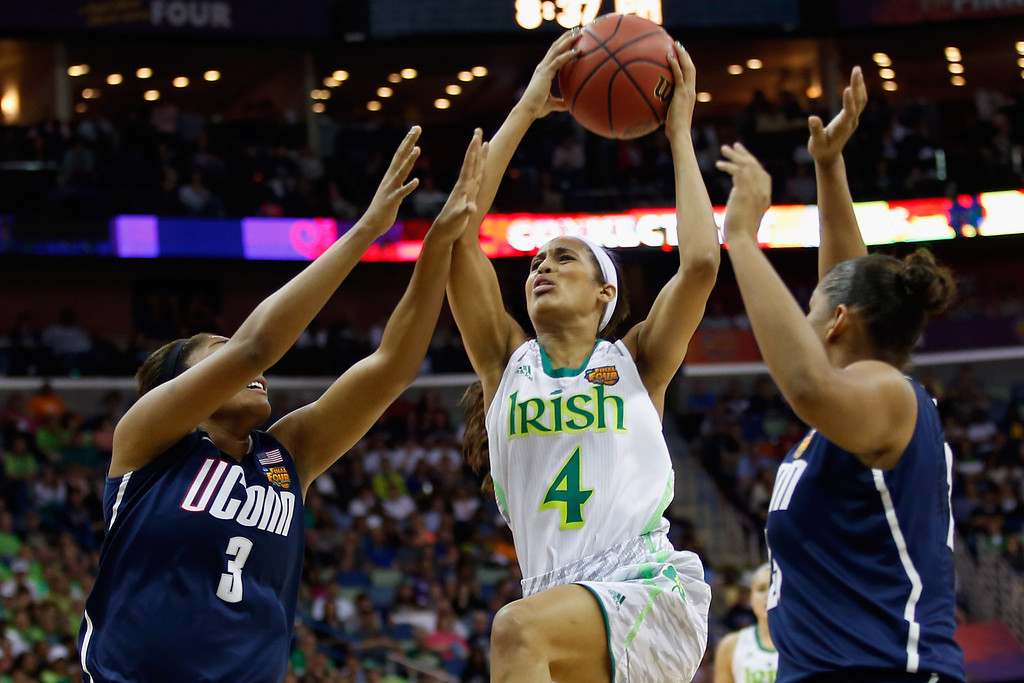 . Skylar Diggins #4 of the Notre Dame Fighting Irish makes a shot over Morgan Tuck #3 of the Connecticut Huskies during the National Semifinal game of the 2013 NCAA Division I Women\'s Basketball Championship at the New Orleans Arena on April 7, 2013 in New Orleans, Louisiana.  (Photo by Chris Graythen/Getty Images)