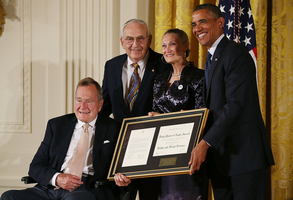 . Former President George H. W. Bush (L) and U.S. President Barack Obama (R) pose with Floyd Hammer (2nd-L) and Kathy Hamilton (2nd-R) after they received the Daily Point of Light Award during an event in the East Room during an event at the White House, July 15, 2013 in Washington, DC. Bush joined President Obama in hosting the event to honor the 5,000th Daily Point of Light Award winner.  (Photo by Mark Wilson/Getty Images)