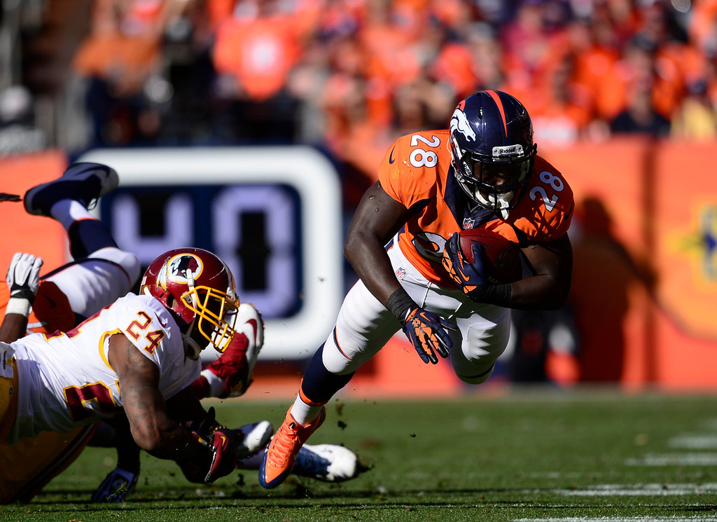 . DENVER, CO - OCTOBER 27: Denver Broncos running back Montee Ball (28) is tripped up by Washington Redskins strong safety Bacarri Rambo (24) in the second quarter. The Denver Broncos take on the Washington Redskins at Sports Authority Field at Mile High in Denver on October 27, 2013. (Photo by AAron Ontiveroz/The Denver Post)