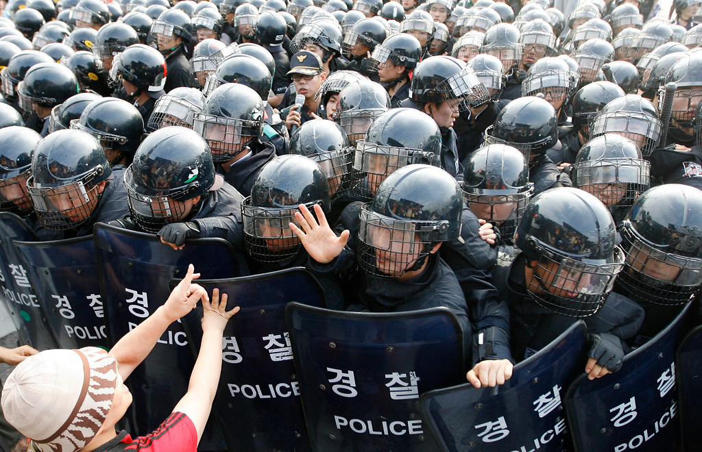 . A supporter of striking workers at Ssangyong Motor scuffles against policemen as the police block a protest in front of the automaker\'s main plant in Pyeongtaek, about 70 km (40 miles) south of Seoul, June 27, 2009.  REUTERS/Lee Jae-Won