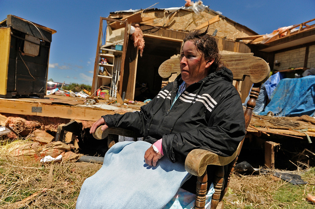 . Lisa Alba\'s family makes her sit down outside her home, Friday April, 27, 2012, after she got back from the hospital. Alba was thrown from her home in Lamar by a tornado. She had bruising on her face and hurt her arm. RJ Sangosti, The Denver Post