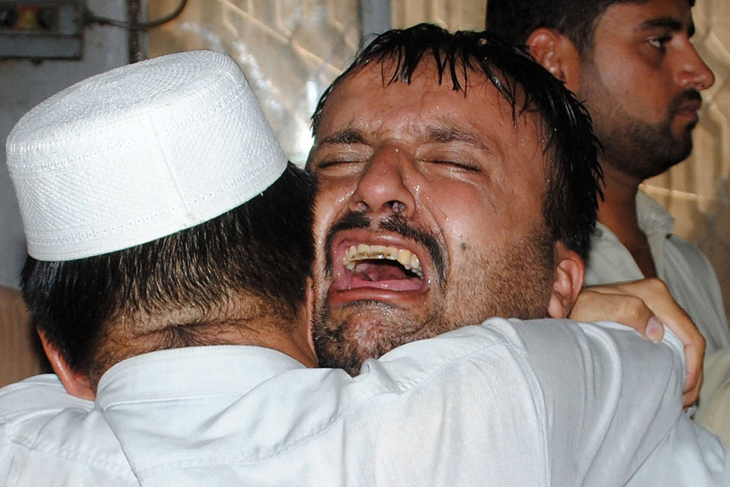 . Pakistani men mourn the killing of their relatives at a hospital after a bomb explosion in Peshawar on September 29, 2013.  AFP PHOTO /  A. MAJEED/AFP/Getty Images