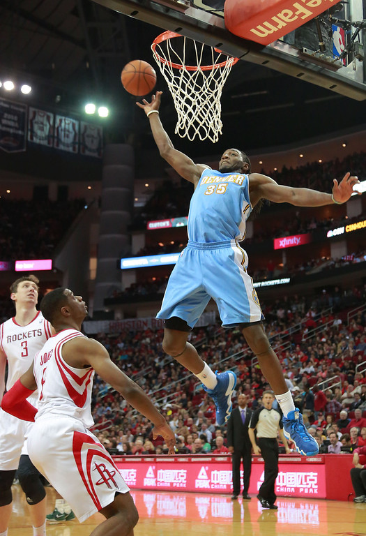 . Denver Nuggets forward Kenneth Faried prepares to score on a pass above the rim as Houston Rockets center Omer Asik (3) and forward Terrence Jones watch during the first half of an NBA basketball game in Houston on Sunday, April 6, 2014. (AP Photo/Richard Carson)