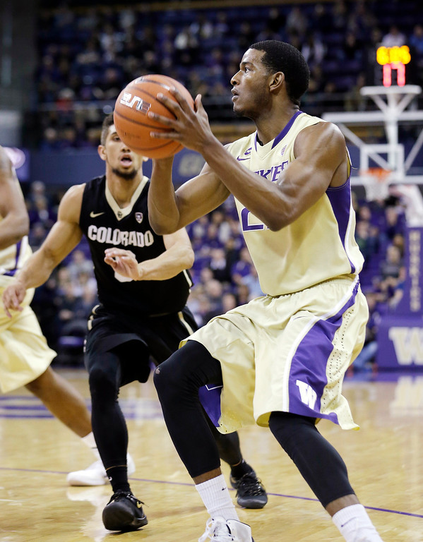 . Washington\'s C.J. Wilcox, right, drives past Colorado\'s Askia Booker in the second half of an NCAA men\'s basketball game Sunday, Jan. 12, 2014, in Seattle. Washington won 71-54. (AP Photo/Elaine Thompson)