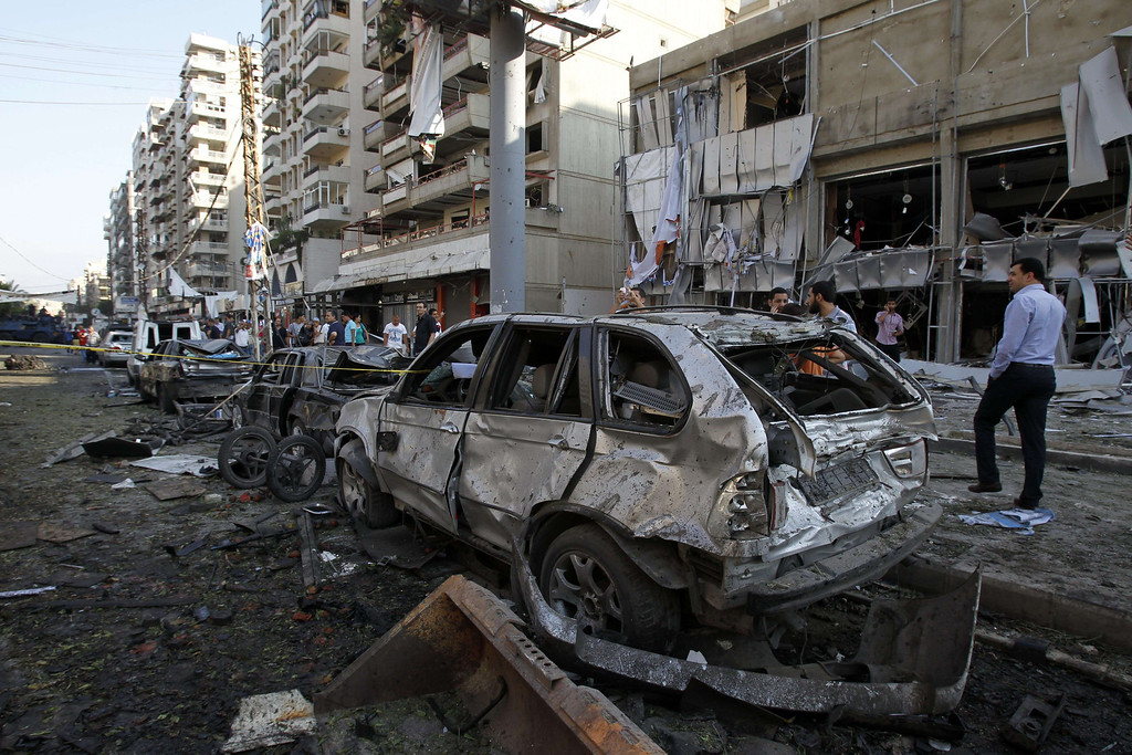 . Lebanese civilians walk past the debris next to the site of a blast outside the Al-Salam mosque in the northern city of Tripoli on August 23, 2013.  AFP PHOTO/ANWAR AMRO/AFP/Getty Images